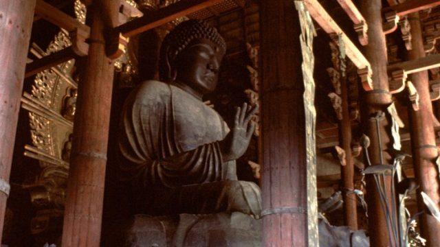 Large sculpture of Gautama Buddha set in timber architecture.