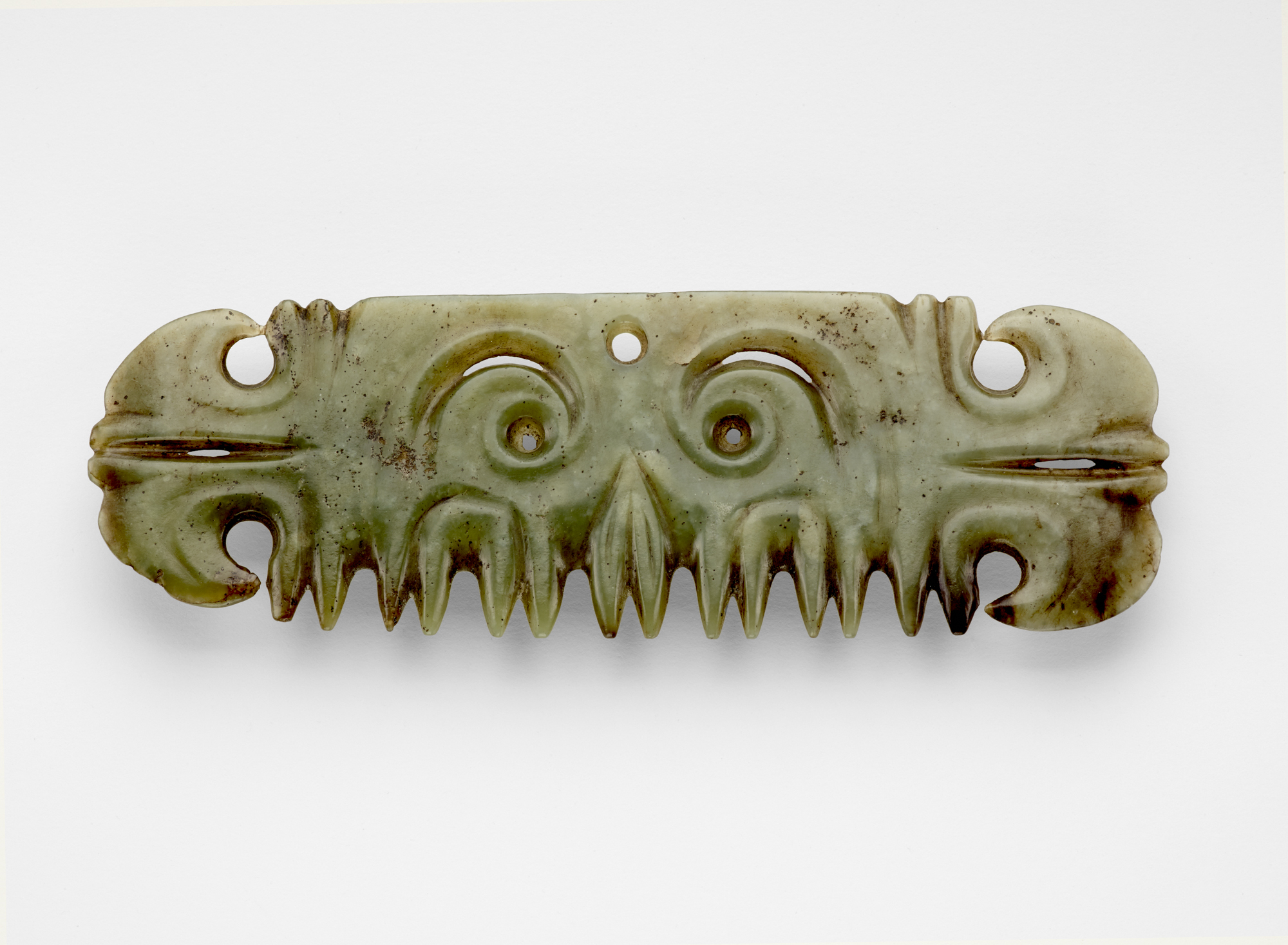 green stone in the shape of a rectangle with a face like carving