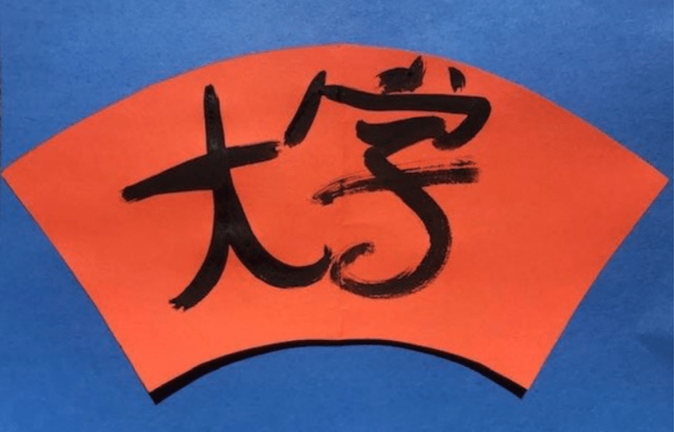 orange paper on a blue background in the shape of a fan with chinese characters drawn on it