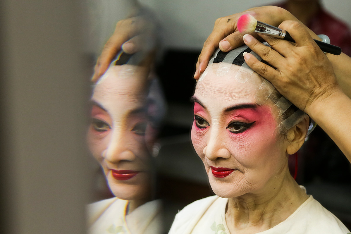 photo of a woman with makeup looking in a mirror