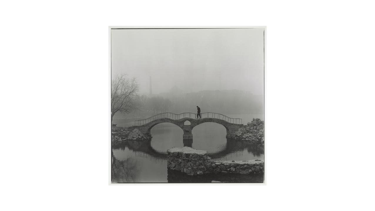 photo of man walking over a bridge in fog